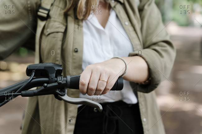 Young woman holding handlebar of electric bicycle