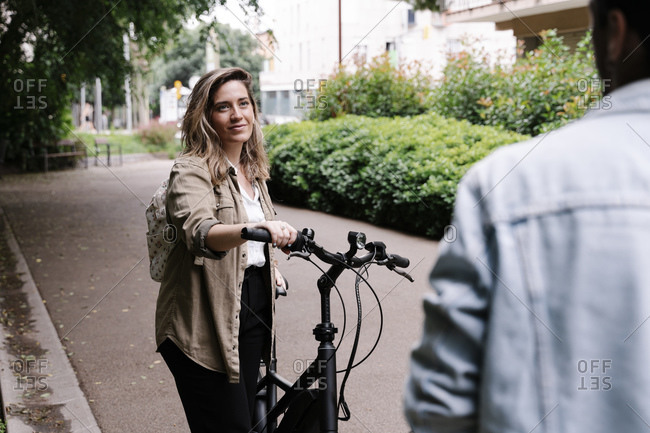 Beautiful woman looking at boyfriend while standing with electric bicycle on road