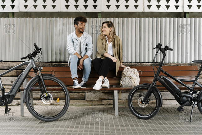 Couple sitting on bench while electric bicycles parked on footpath