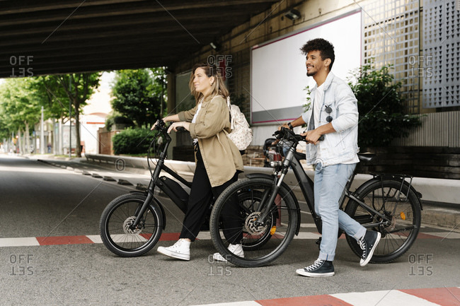 Couple crossing road with electric bicycles in city
