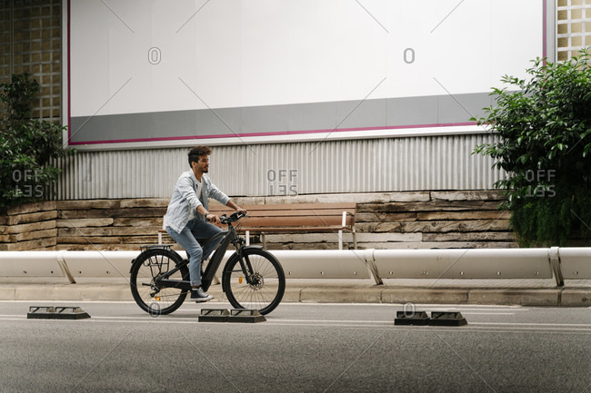 Young man riding electric bicycle on road in city