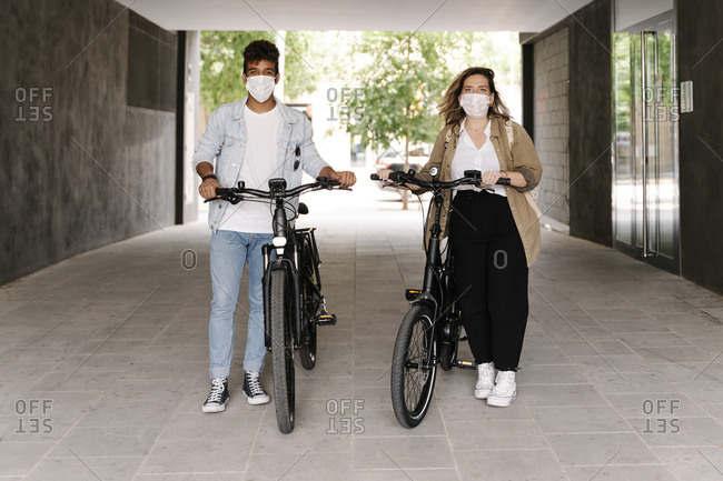 Couple in protective face masks standing with electric bicycles on footpath