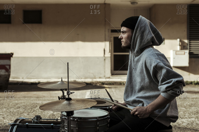 Handsome musician wearing hood playing drums at back yard