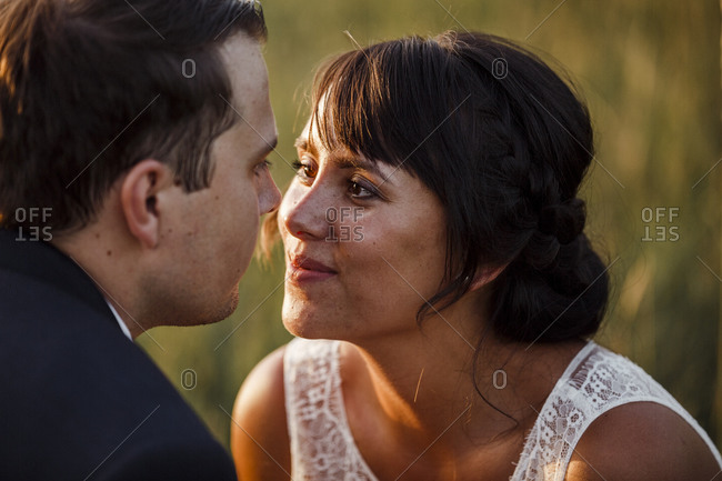 Close-up of bridal couple looking at each other during sunset
