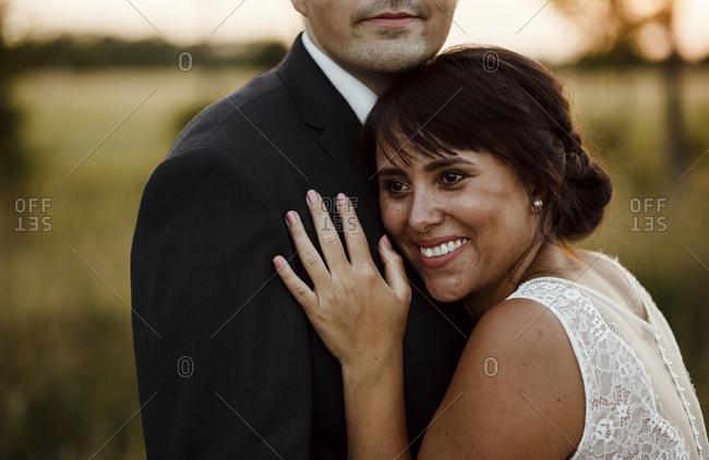 Happy beautiful bride embracing bridegroom during sunset