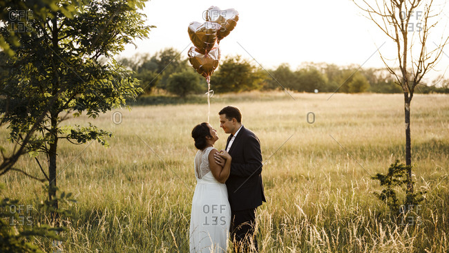 Bridal couple holding heart shape helium balloons while standing in field during sunset