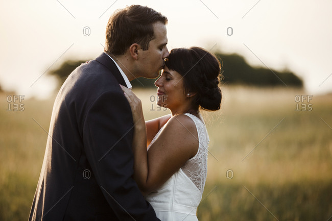 Bridegroom kissing bride on forehead while standing in field during sunset
