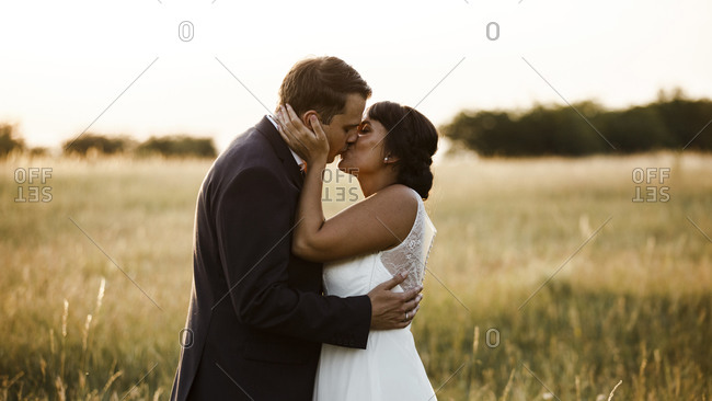Affectionate young bridal couple kissing at field during sunset
