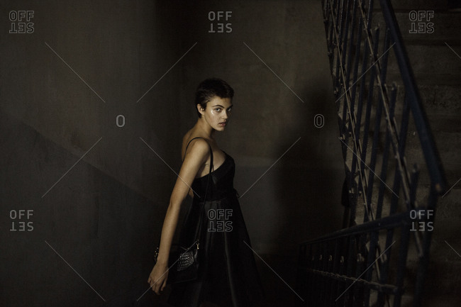 Fashionable young woman moving down on staircase