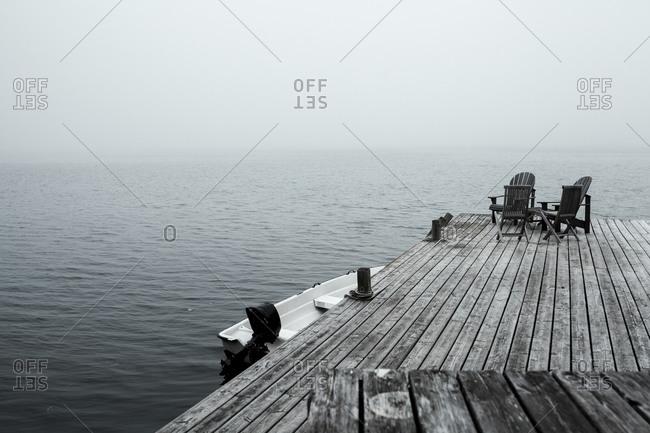 Empty deck chairs on coastal jetty at foggy dawn