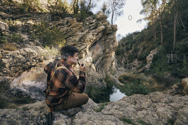 Bush crafter smoking pipe while sitting on rock formation