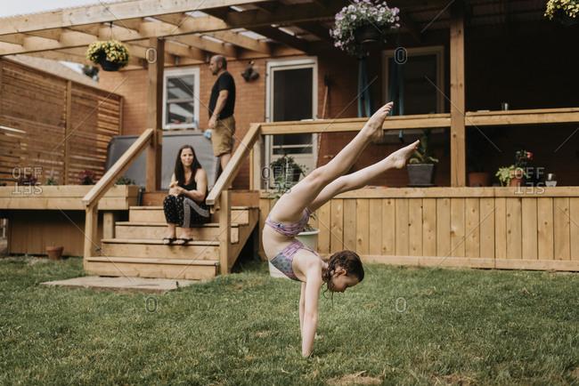 Girl doing acrobatics in garden- parents on terrace
