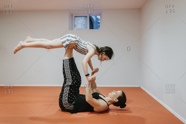 Mother and daughter doing acrobatics in cellar