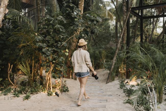 Female tourist with camera walking barefoot on sandy way