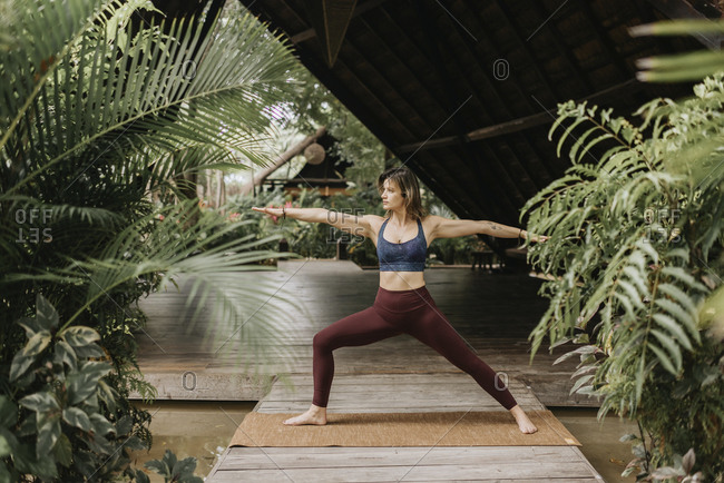 Woman practicing warrior pose - Offset