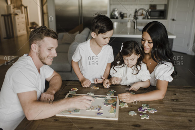 Smiling parents solving puzzle with kids over table at home