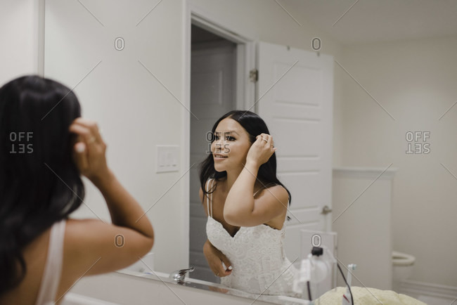 Reflection of smiling woman with hand in hair seen through mirror in bathroom