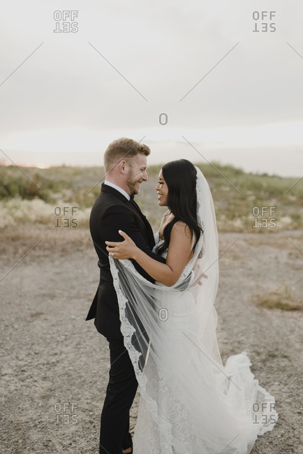 Smiling bride and groom looking at each other in field against sky