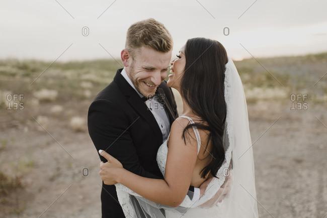 Happy groom embracing bride while standing in field against sky