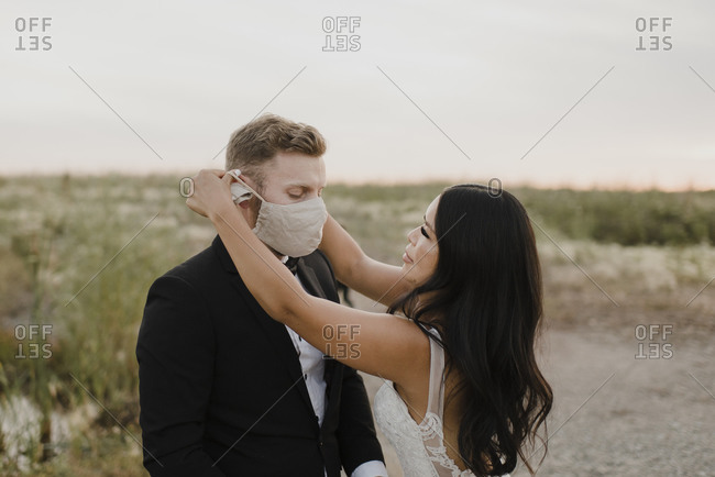 Bride covering groom's face with protective mask during COVID-19
