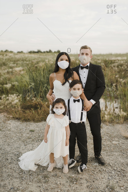 Parents and children in wedding dress wearing protective face mask while standing in field during COVID-19