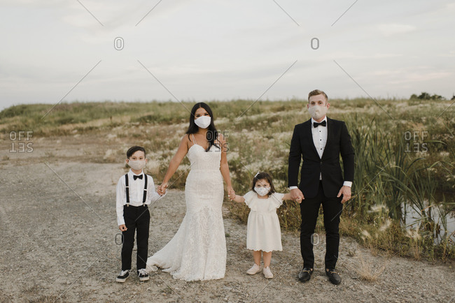 Parents and children in wedding dress wearing face mask while standing in field during COVID-19