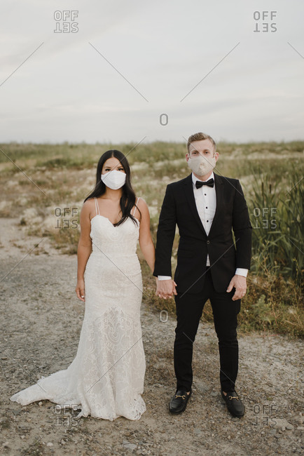 Bride and groom with protective face mask standing in field during COVID-19