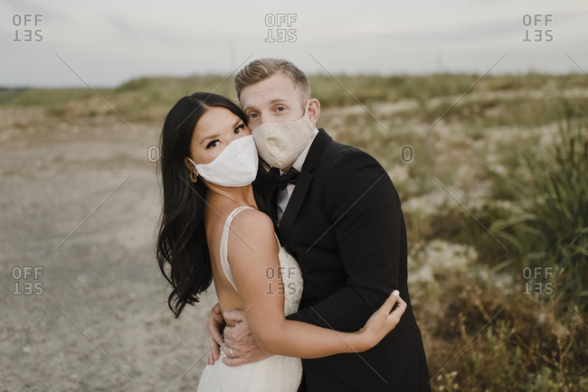 Bride with groom wearing protective face mask in field during COVID-19