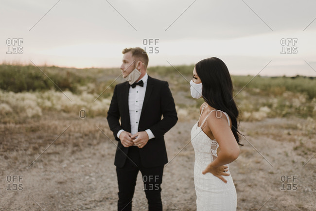 Bride with groom wearing protective face mask while looking away in field during COVID-19