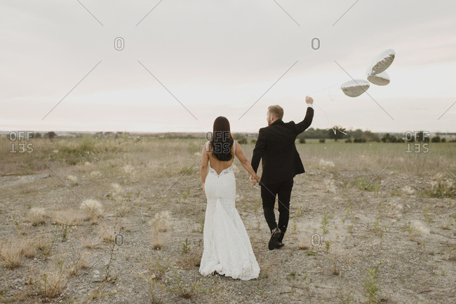 Bride and groom with heart shape balloons walking against sky