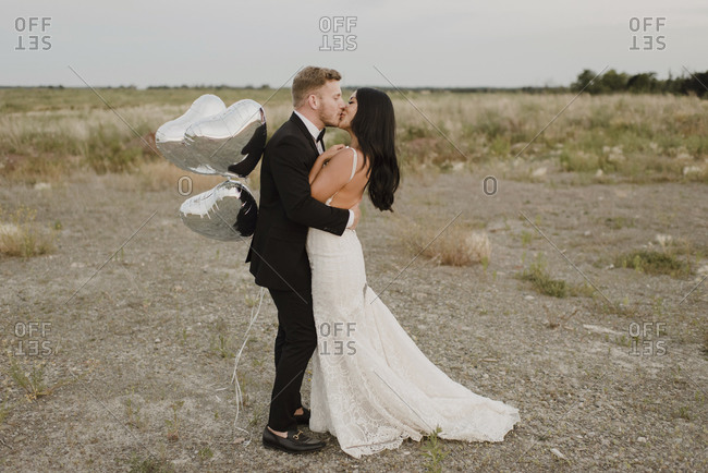 Smiling groom with heart shape balloons kissing bride against sky