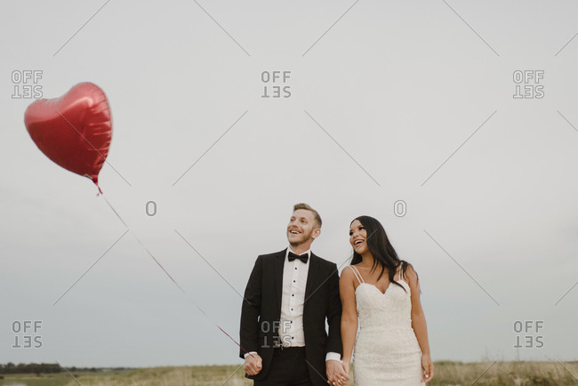 Happy bride and groom with heart shape balloon against sky
