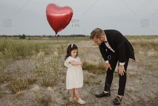 Father talking to sad daughter with heart shape balloon in field against clear sky