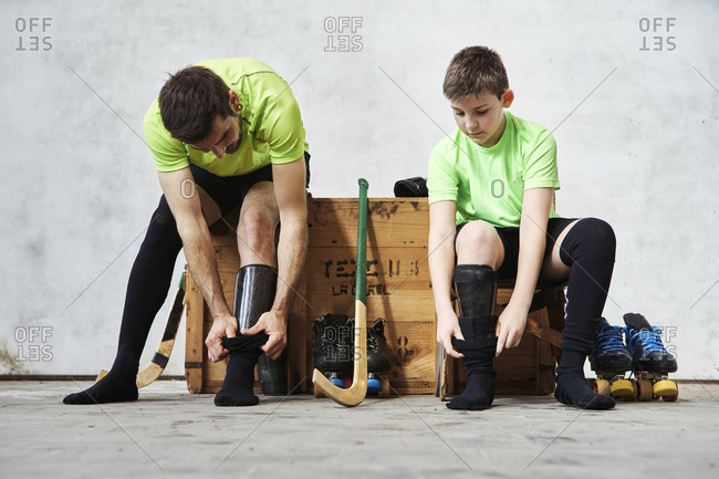 Father and son wearing socks while sitting on wooden box at court