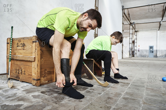 Mature man and son wearing socks while sitting on wooden box at court