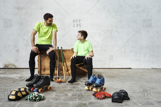 Father and son talking while sitting on wooden box by sports equipment against wall at court