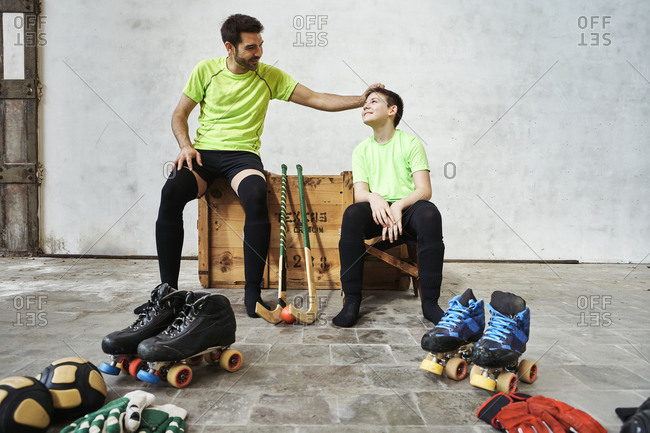 Father sharing light moment with while sitting on wooden box by sports equipment against wall at court