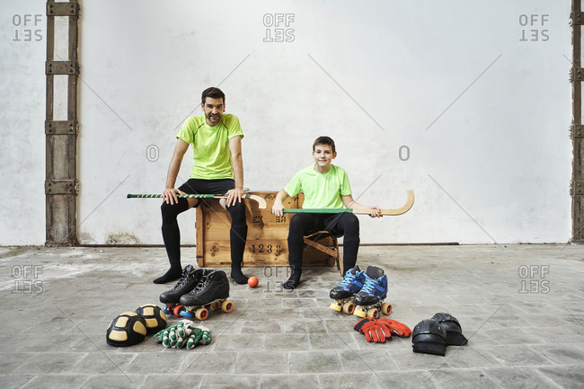 Father and son sitting with hockey sticks on wooden box by sports equipment against wall at court
