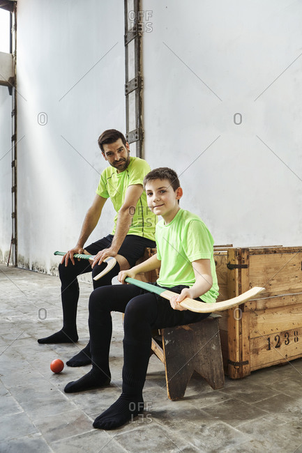 Confident boy and father sitting with hockey sticks against wall at court