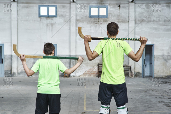 Father and son in uniform holding hockey sticks at sports court