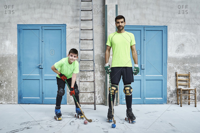 Mature man and his son holding hockey sticks against doors at court