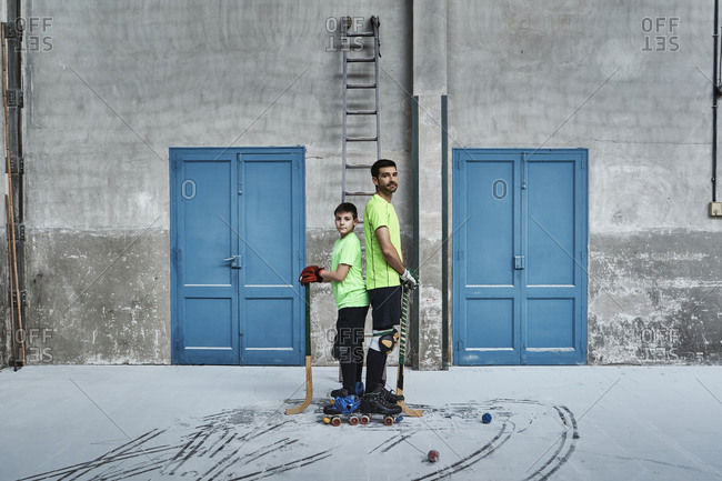 Father and son standing back to back while holding hockey sticks by doors at court