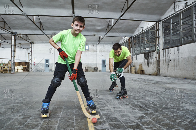 Mature man with son practicing roller hockey on court