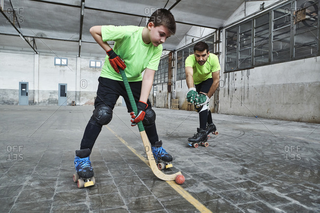 Boy practicing roller hockey with father on court