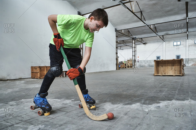Boy practicing roller hockey during training at court