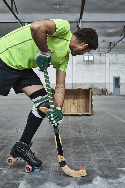 Mature male athlete practicing roller hockey while aiming at wooden box