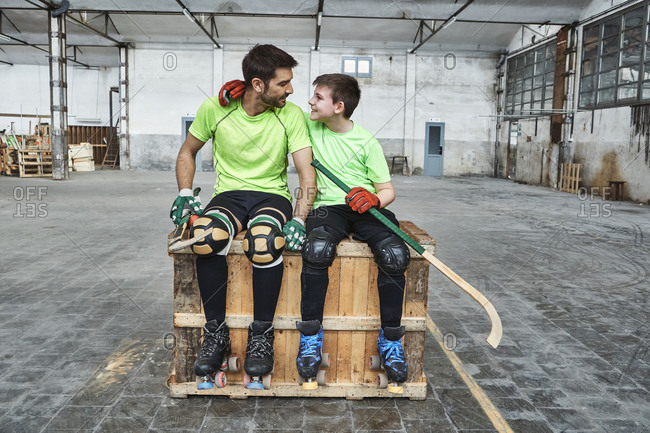 Smiling boy with arm around father while sitting with hockey sticks on wooden box at court