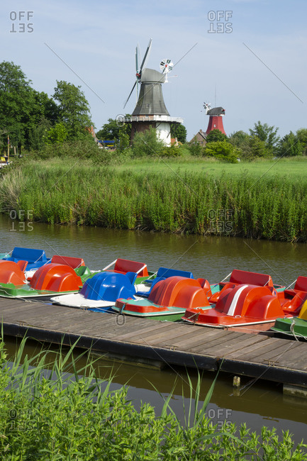 Germany- Lower Saxony- Krummhorn- Pedal boats moored along riverbank jetty with windmills in background