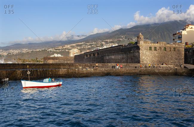 March 26, 2019: Spain- Canary Islands- Puerto de la Cruz- Boat floating in front of Bateria de Santa Barbara fort