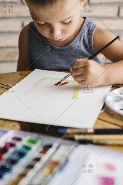 Cute boy holding paintbrush while painting on paper at home